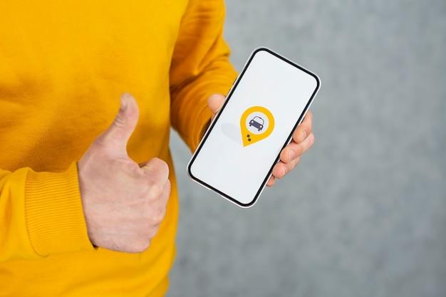 남자는 흰색 화면과 위치 정보 아이콘이있는 스마트 폰을 보유하고 있습니다.