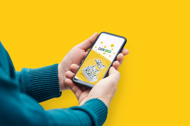 Man holds smartphone with banner cash back on yellow background.