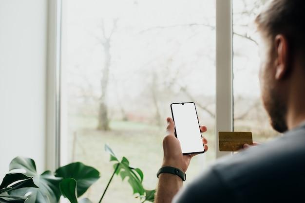 男は白い画面と銀行カードでスマートフォンを持っています。