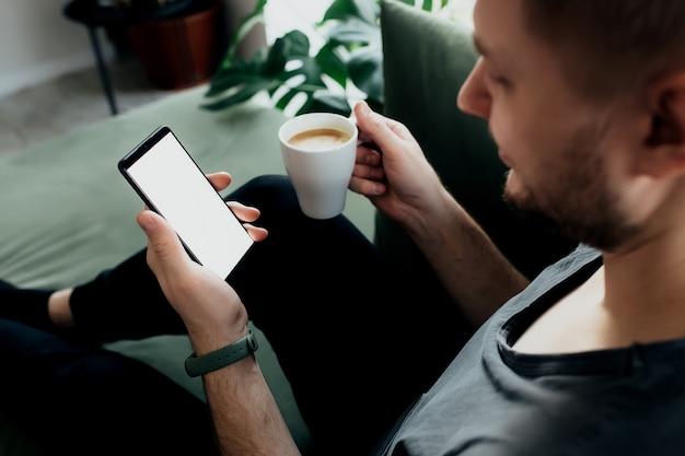 男は白い画面とコーヒーカップでスマートフォンを持っています。
