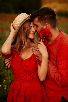 Man holds tender beautiful woman standing with her on the green field with red poppies