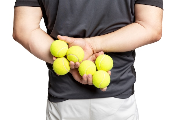 A man holds tennis balls in his hands.