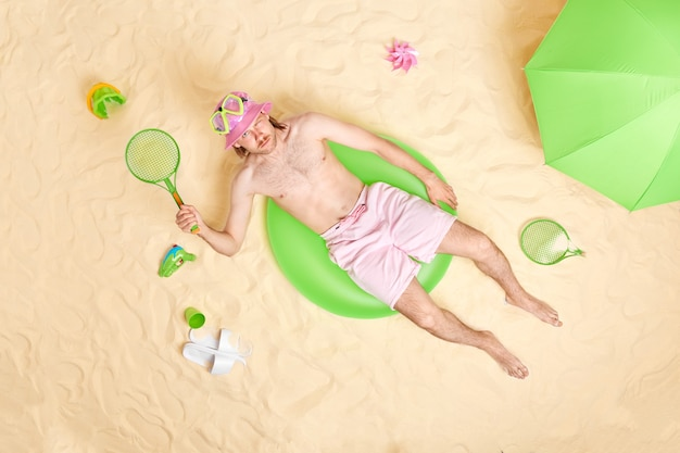 Man holds tennis racket lies in sun at beach surrounded by sand toys plays active games at seaside poses on green inflated swimring enjoys holidays