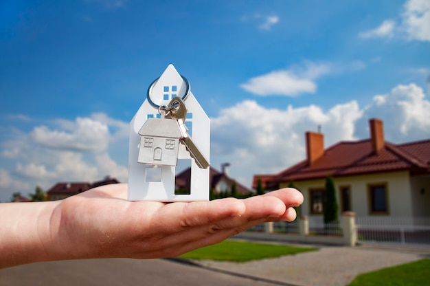 Мужчина держит в руках ключи от дома на фоне жилых домов. концепция покупки и аренды квартир.
