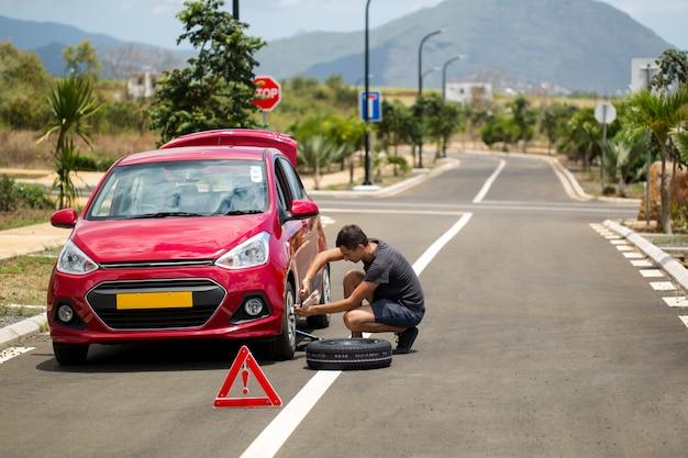남자는 고장난 자동차에 대한 여분의 타이어를 보유