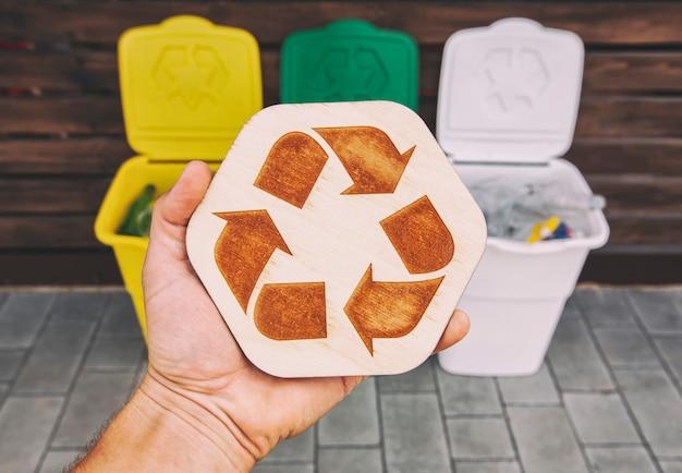 男はゴミを分別するために3つのゴミ箱の前に手に木製のリサイクルサインを持っています