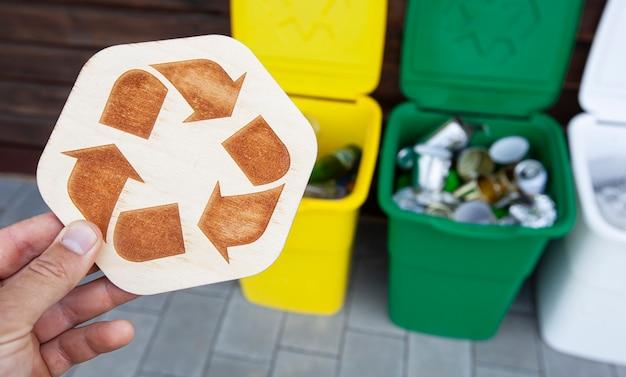 男はゴミを分別するために3つのゴミ箱の前に木製のリサイクルサインを手に持っています