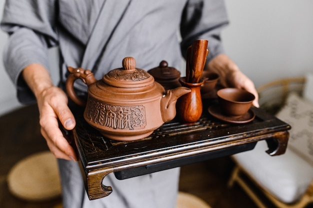 A man holds a tray with a set for a chinese tea ceremony