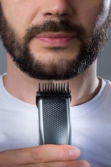 A man holds a trimer near his beard