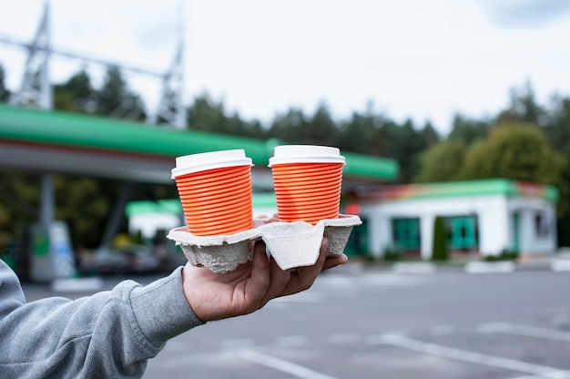 A man holds two cups of coffee in his hands at a gas station.