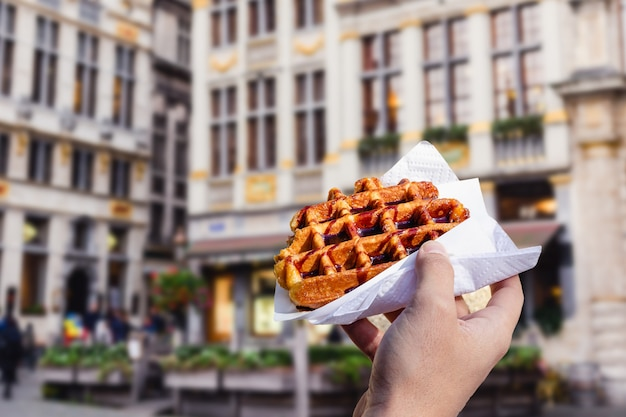 Man holds waffle with chocolate sauce on the background of city