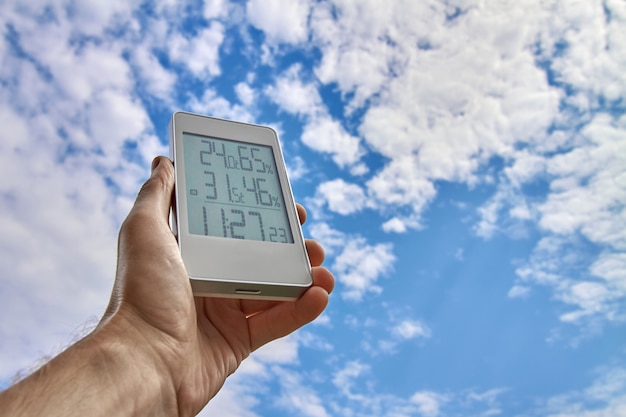 A man holds a weather station device on a background of sky and clouds