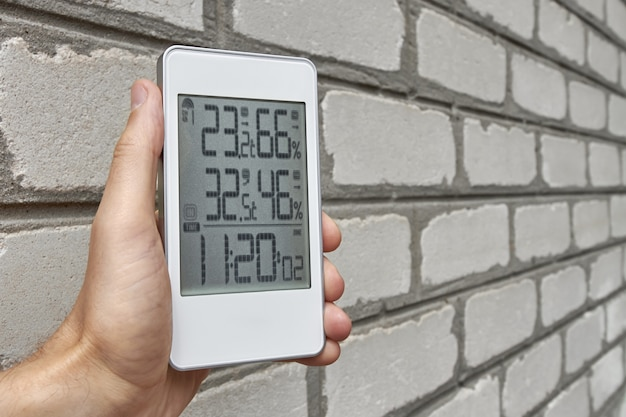 A man holds a weather station device with weather conditions inside and outside