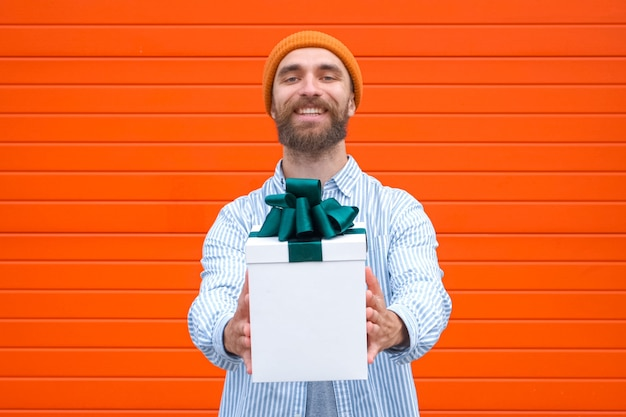 Man holds white box with green bow