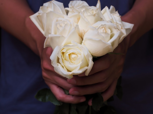 Man holds white rose