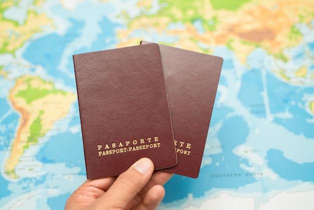 男は手でパスポート、世界地図を保持しています。旅行のコンセプト