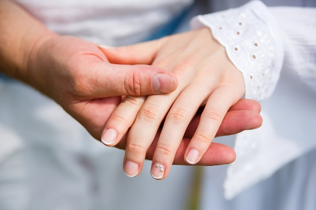 Man holds womans hand in his palm on white