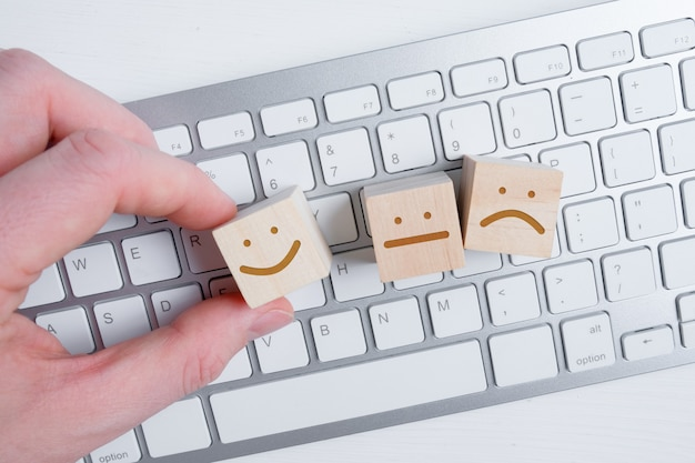 A man holds a wooden cube with a picture of a positive face next to negative and neutral emotions on a keyboard .