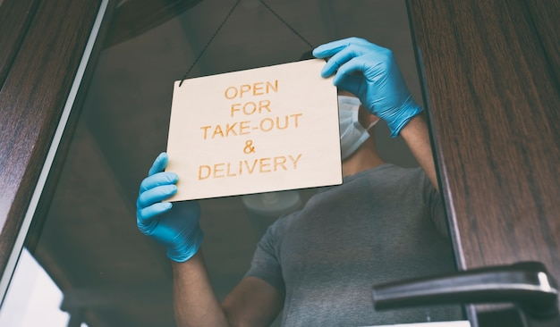 Man holds the wooden sign with text: open for take-out and delivery
