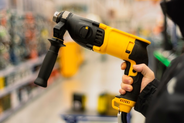 Man holds a yellow drill in his hands for repair work on the background of showcases in a hardware store.