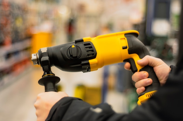 Man holds a yellow puncher for repair work in his hands against the backdrop of showcases in a hardware store.