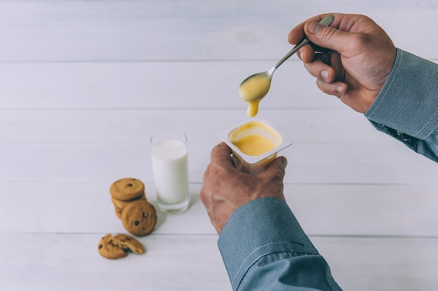 A man holds yogurt in his hand on a space of oatmeal cookies and a glass of milk.