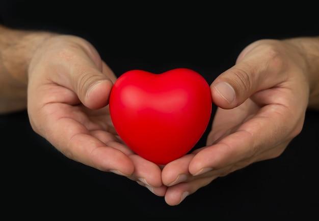 어두운 배경에 붉은 마음을 holging 남자. 사람, 관계, 건강 및 사랑 개념