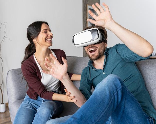 Uomo a casa divertendosi con le cuffie da realtà virtuale accanto alla donna