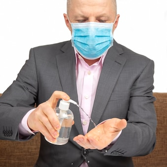 Man at home in quarantine with a medical mask on his face disinfects his hands with an alcohol solution from infection with a virus