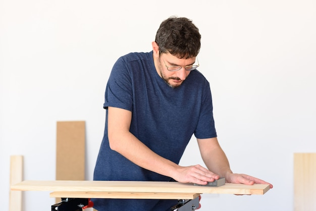 Man at home sanding a wood on a workbench. white background.