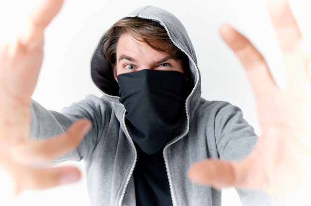 A man in a hood hides his face in a mask bully anonymity