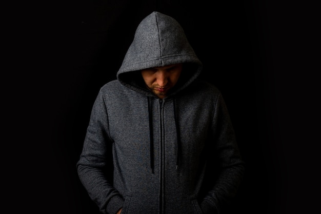 Man in a hood and a hoodie on a dark background.