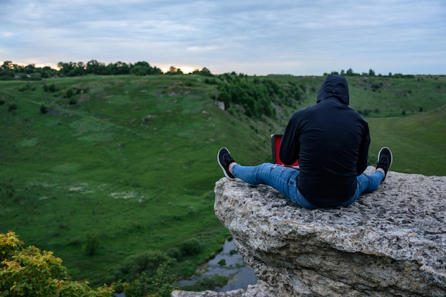 The man in the hood sits on the edge of the cliff, one on a cloudy day