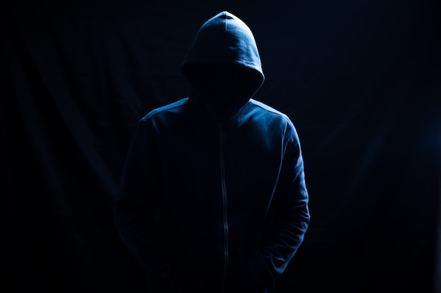 A man in a hood stands on black