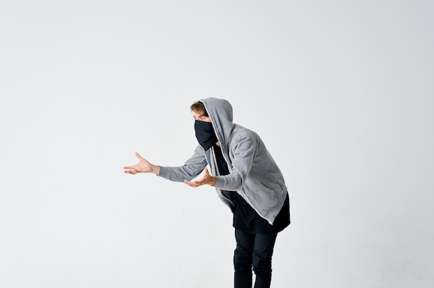 A man in a hood with a mask hides his face bully anonymity theft