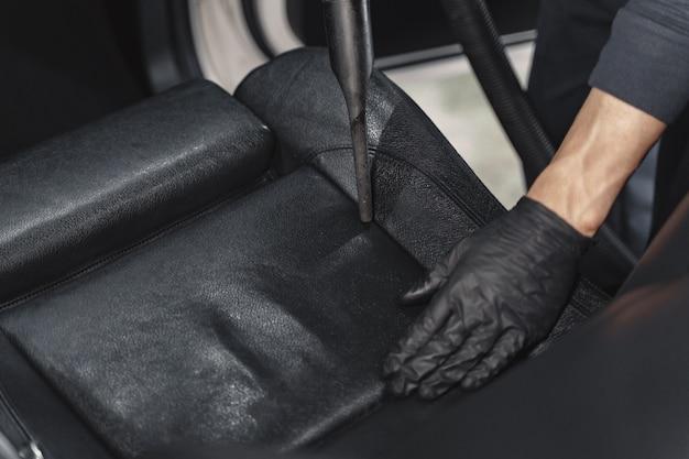 Человек пылесосит кабину автомобиля в гараже