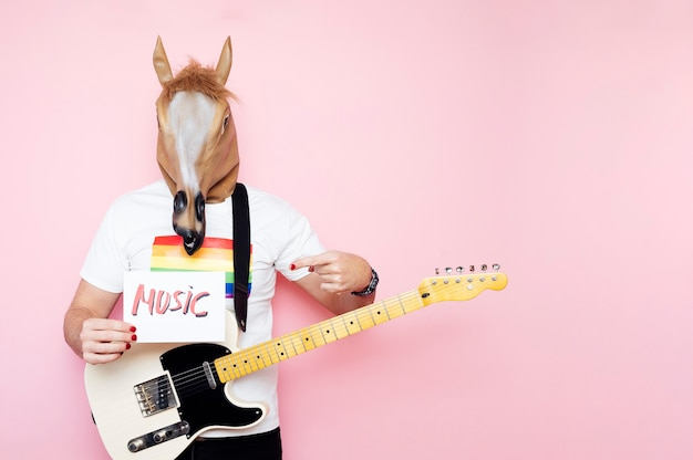 The man in the horse mask and electric guitar points to a sign that says music