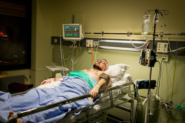 Man on hospital bed for recovery