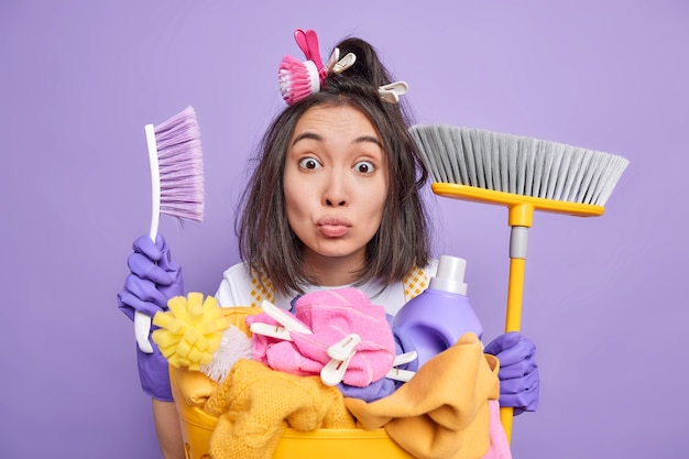 Man housekeeper holds brush and broom uses cleaning agents des laundry at home wears protective rubber gloves stands near basket full of items to wash isolated on purple