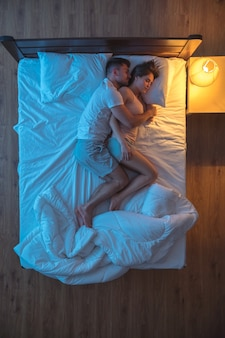 The man hug a woman on the bed. evening night time. view from above