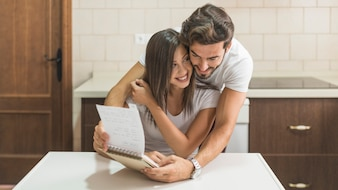 Man hugging cheerful girlfriend with notebook