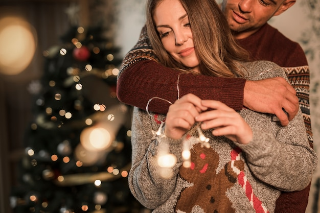 Man hugging cheerful woman in sweaters near christmas tree