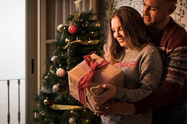 Man hugging cheerful woman with gift box in sweaters near christmas tree