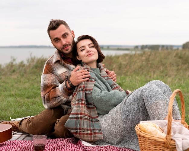 ピクニックでガールフレンドを抱き締める男