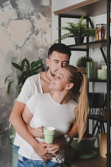 Man hugging her girlfriend holding cup of coffee