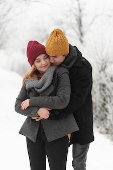 Мужчина обнимает свою подругу в замерзшем парке