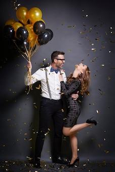 Мужчина обнимает свою танцующую жену на вечеринке