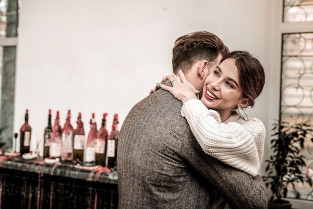 Мужчина обнимает свою улыбающуюся подругу в романтической атмосфере