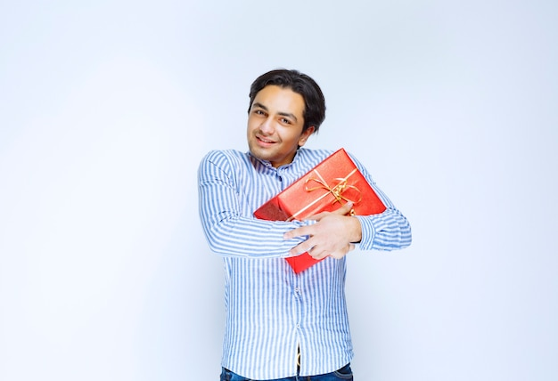 Man hugging his valuable red gift box. high quality photo