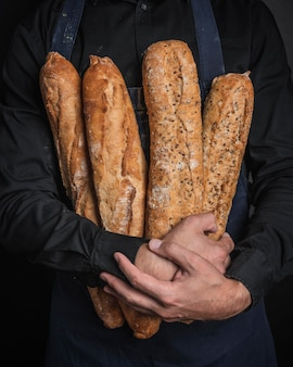 Man hugging loaves of bread